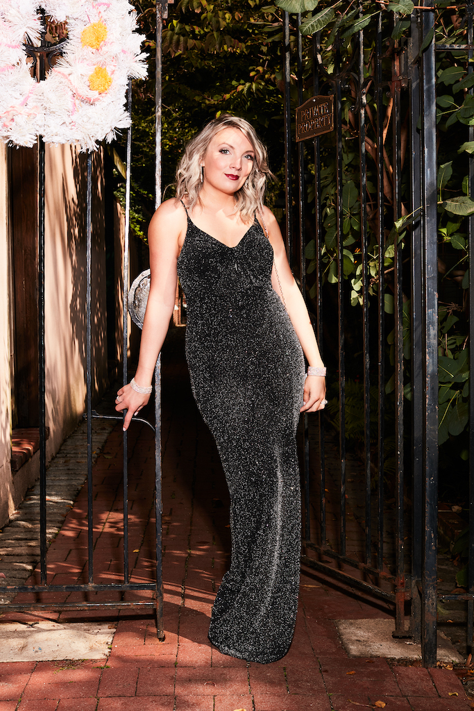 model standing in black glittery sheath holiday party dress