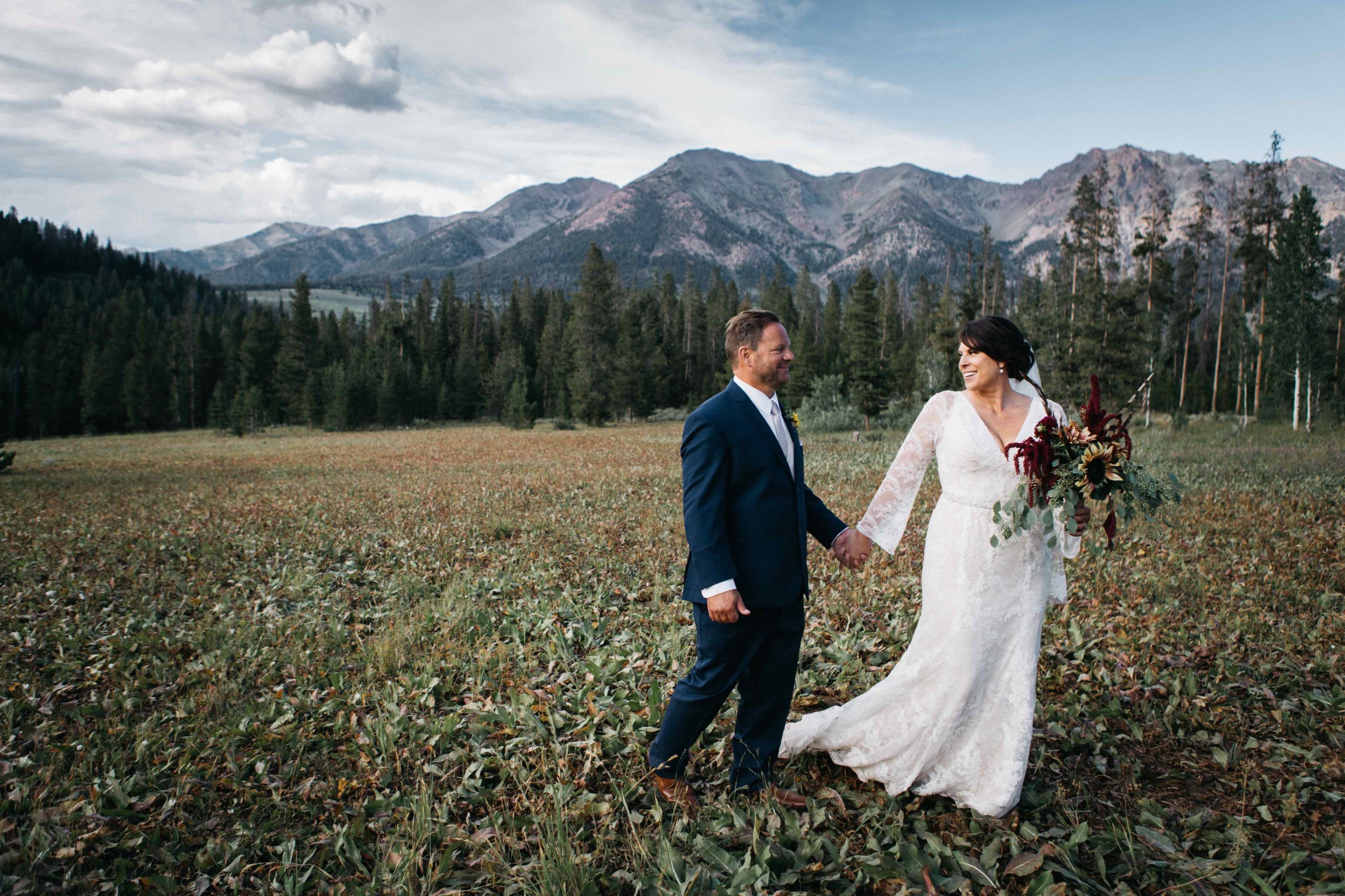 bride and groom holding hands on mountaintop