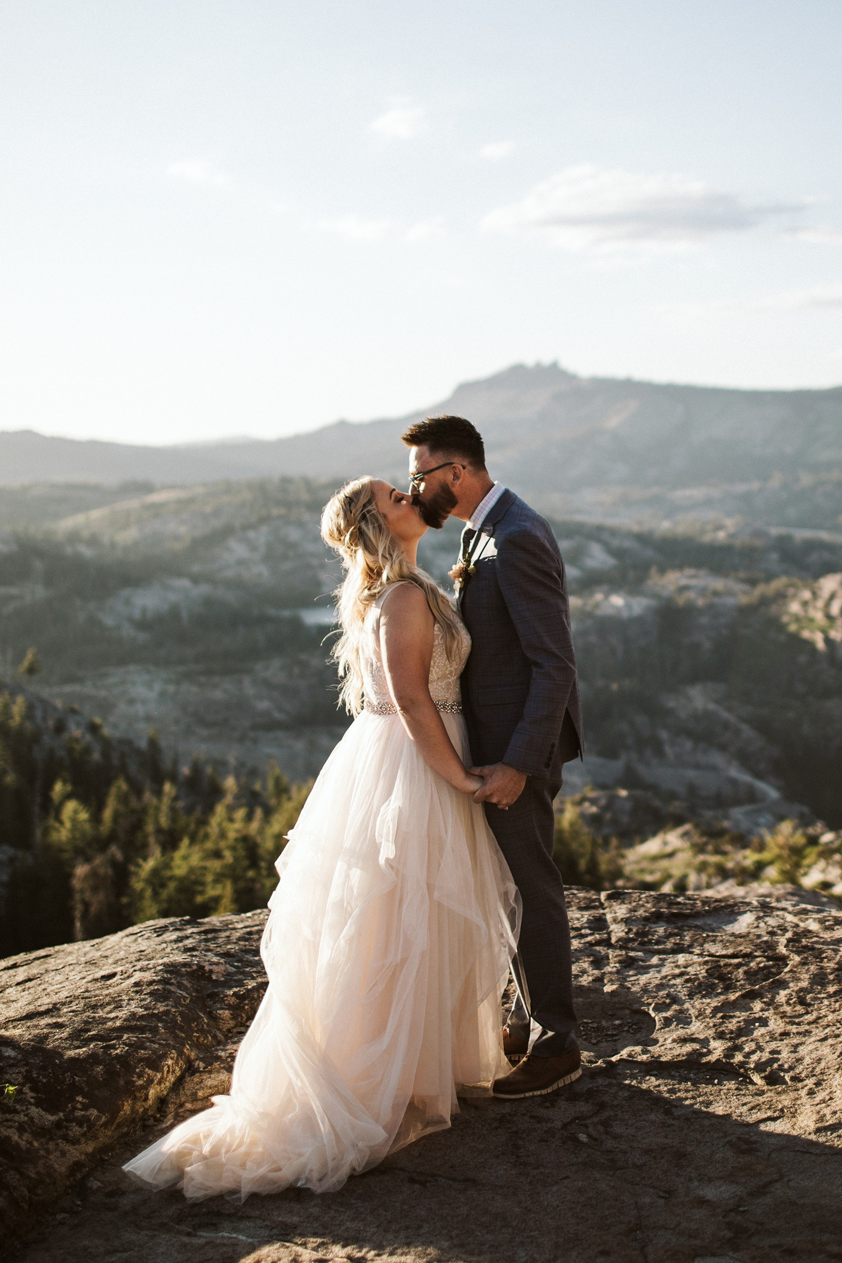 bride and groom kissing on mountaintop