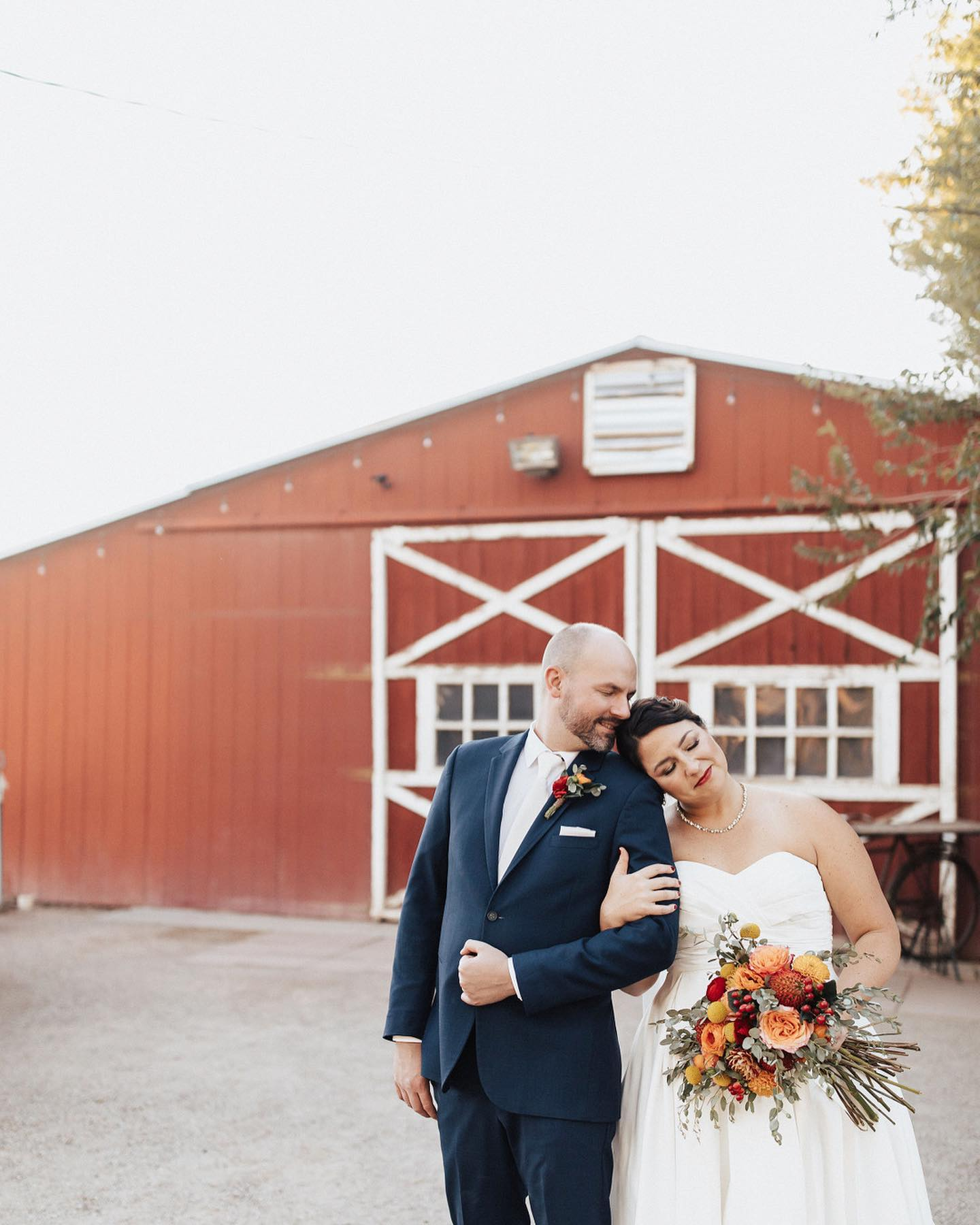 bride and groom in front of red barn