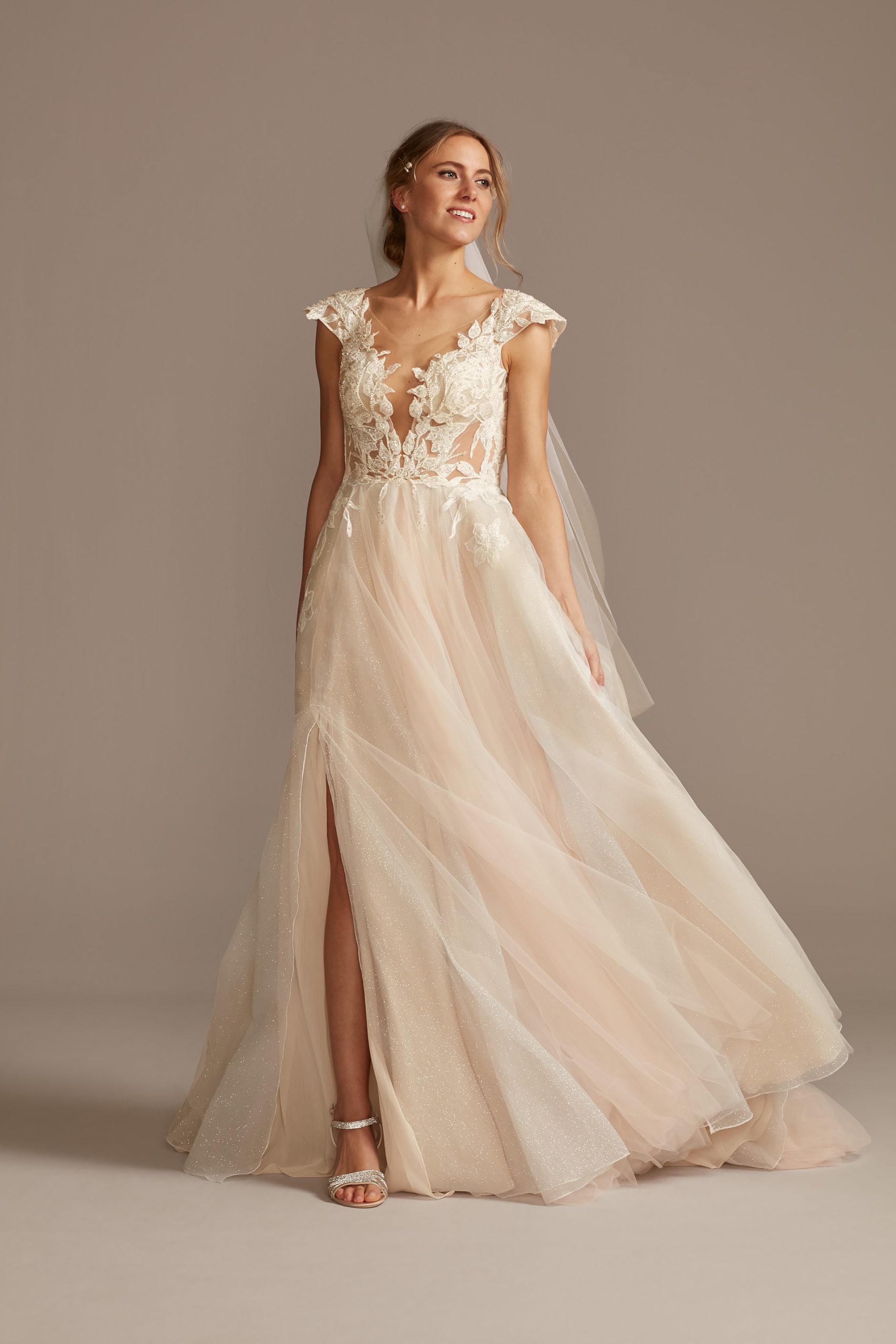 Bride wearing illusion cap sleeve lace appliqued wedding dress