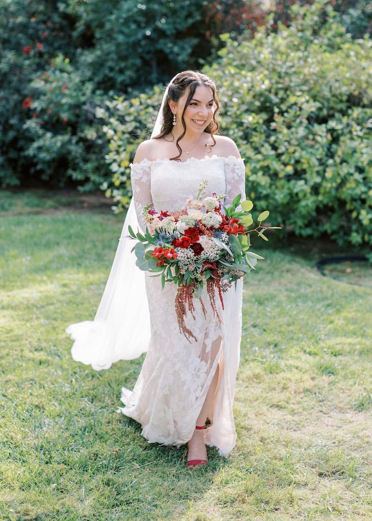 pengantin wanita mengenakan gaun pengantin model sarung bahu dengan motif bunga besar