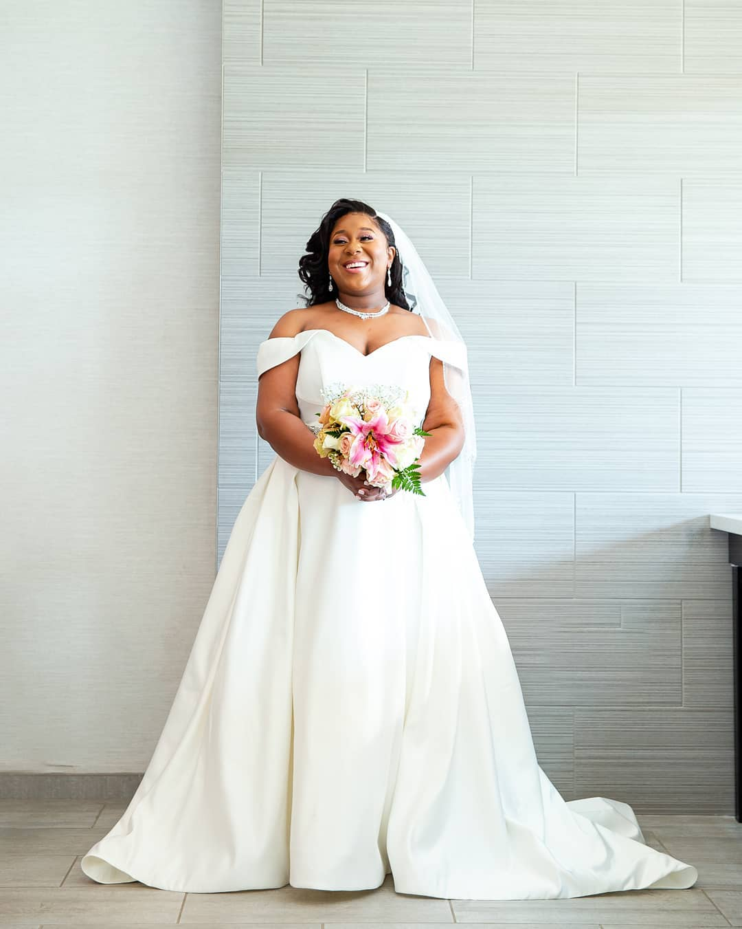 bride wearing an off-the-shoulder satin ball gown