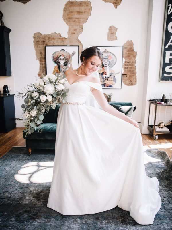 bride wearing an off the shoulder satin ball gown