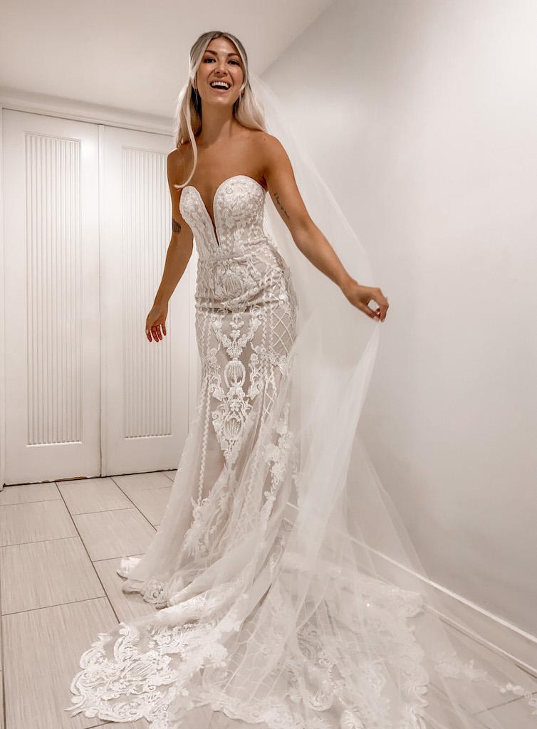 pengantin wanita mengenakan gaun siluet putri duyung dengan appliques renda yang rumit