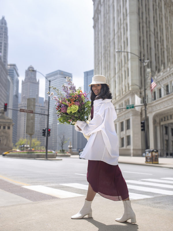 girl walking downtown holding flowers in bridesmaids dress with white dress shirt as a way to restyle a wedding day look