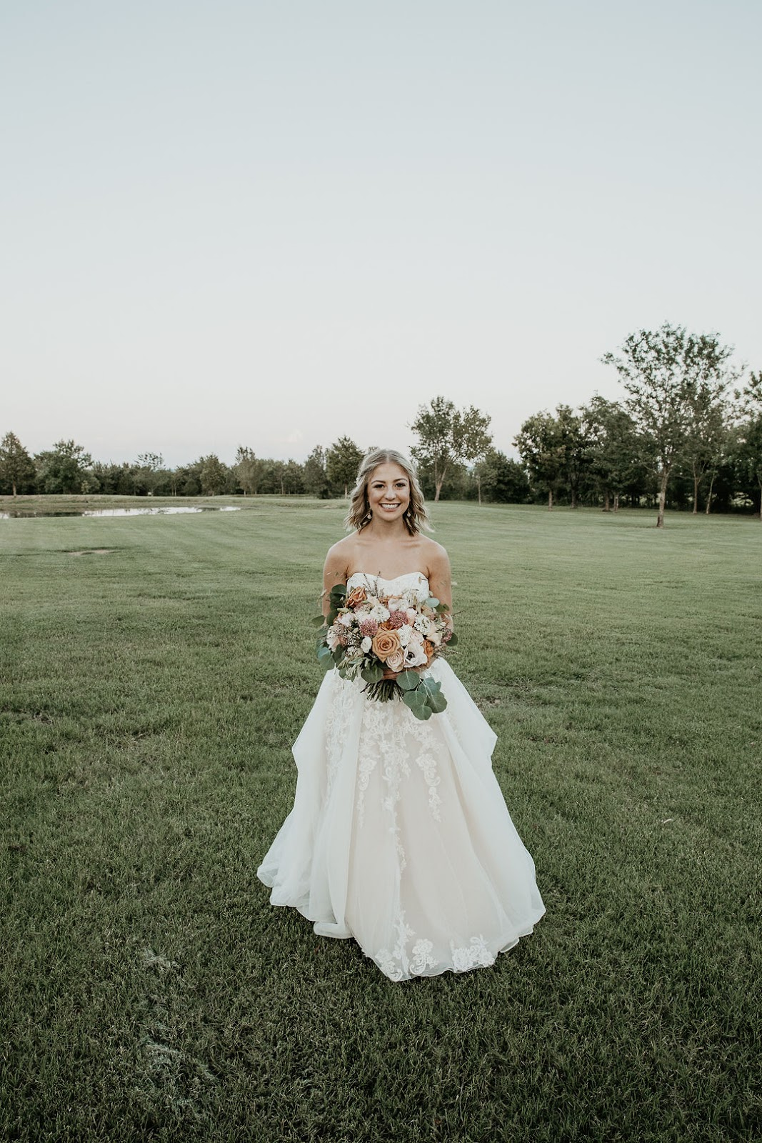 Solo image of bride in dress holding bouquet