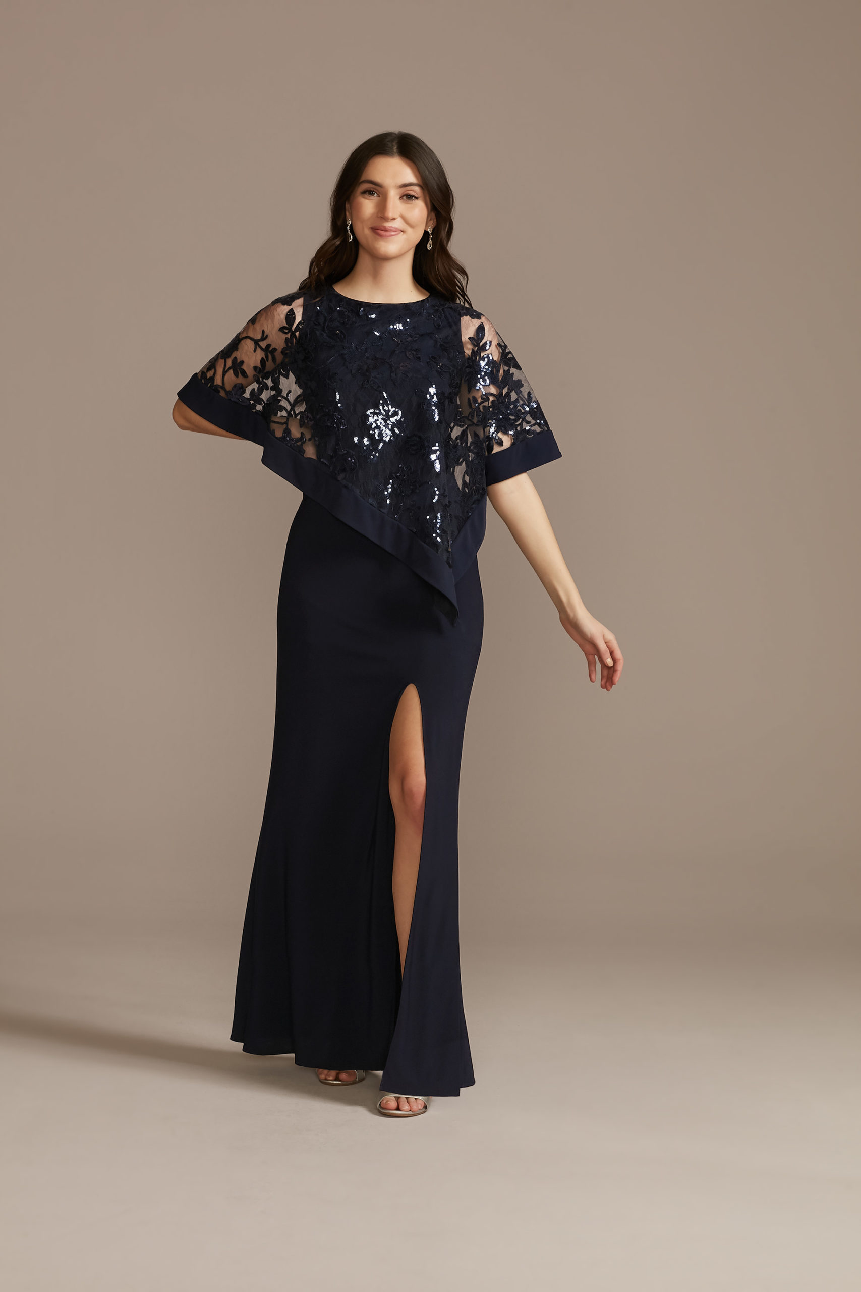 model wearing navy mother of the bride sheath dress with a sequin floral capelet