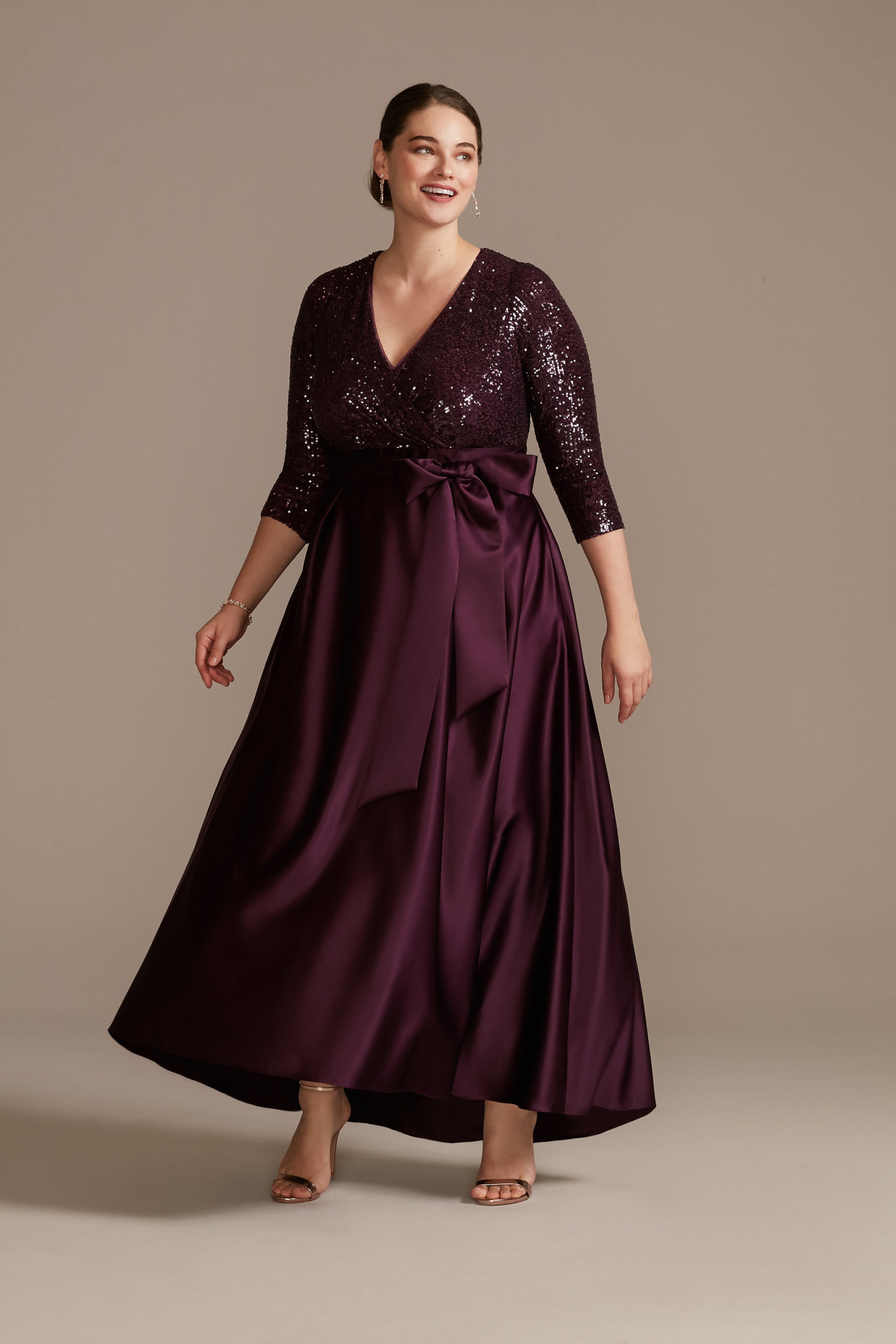 model wearing plum colored mother of the bride sequin and satin ball gown