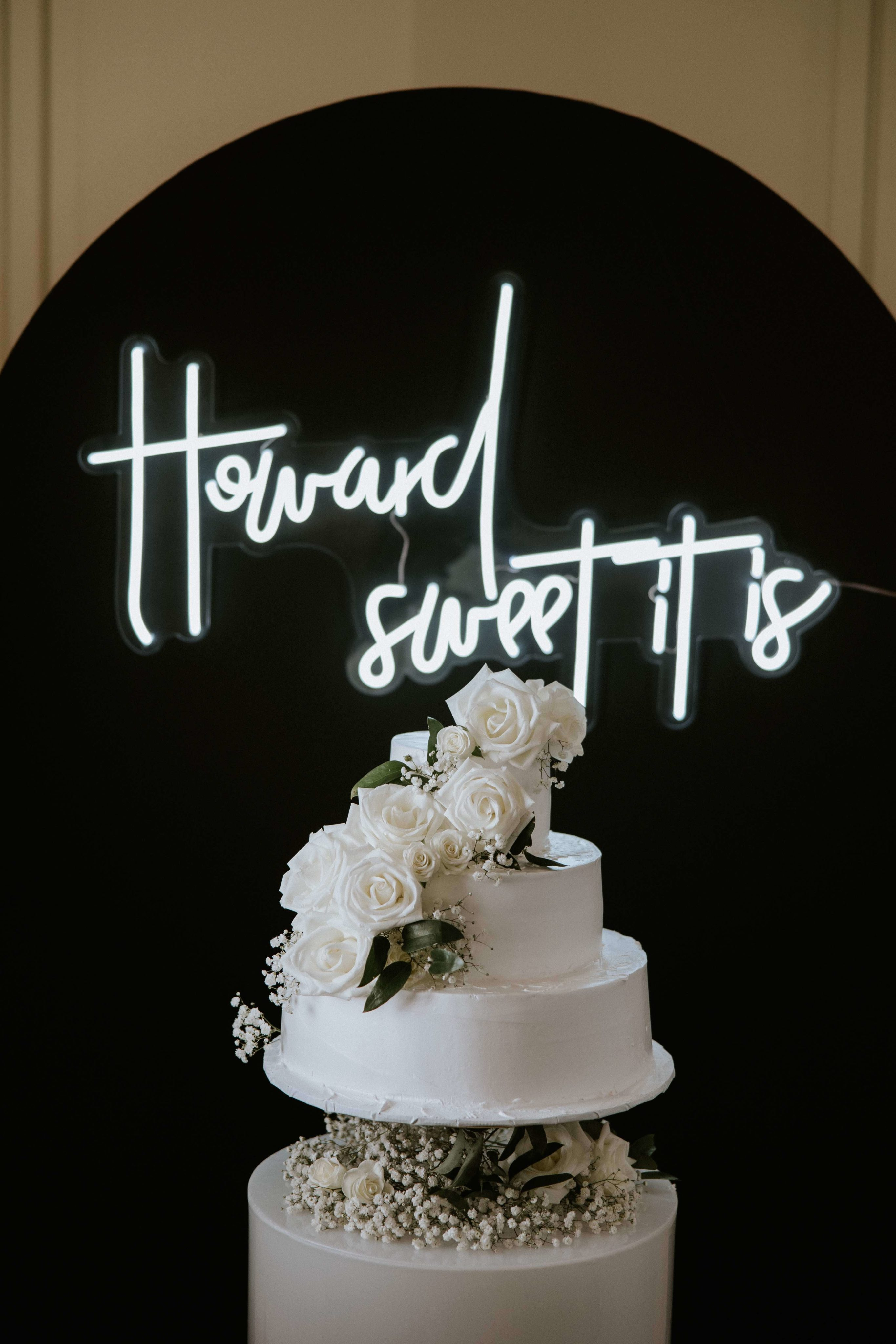 Cake with 'how sweet it is' neon sign in background
