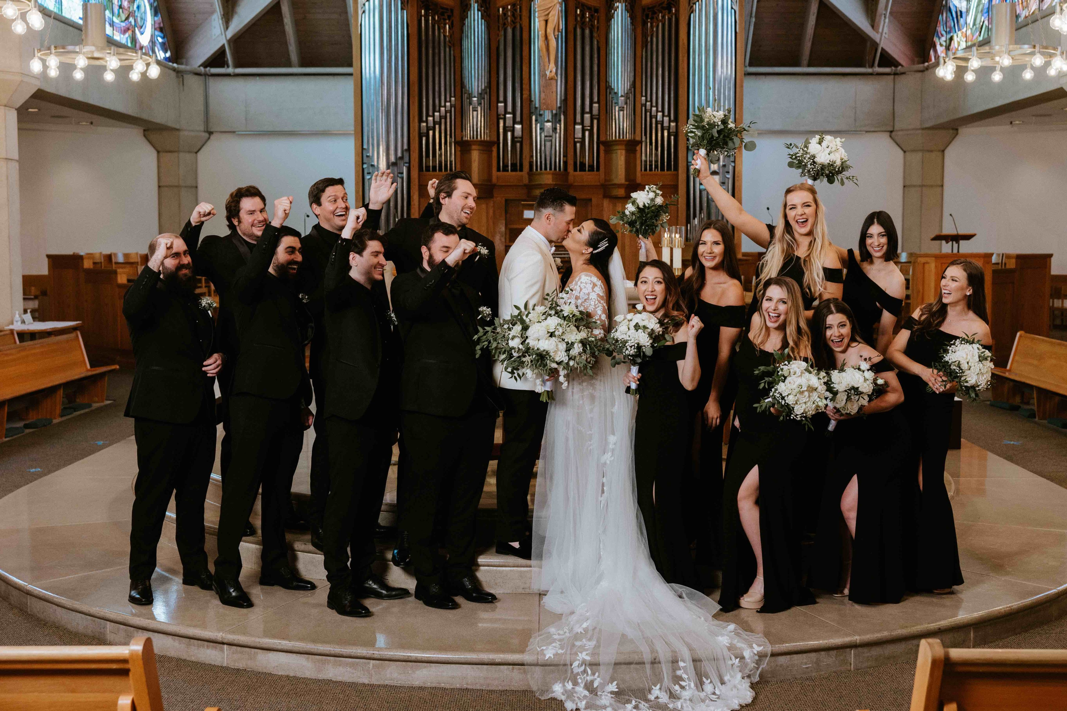 Bride and groom with entire wedding party at altar