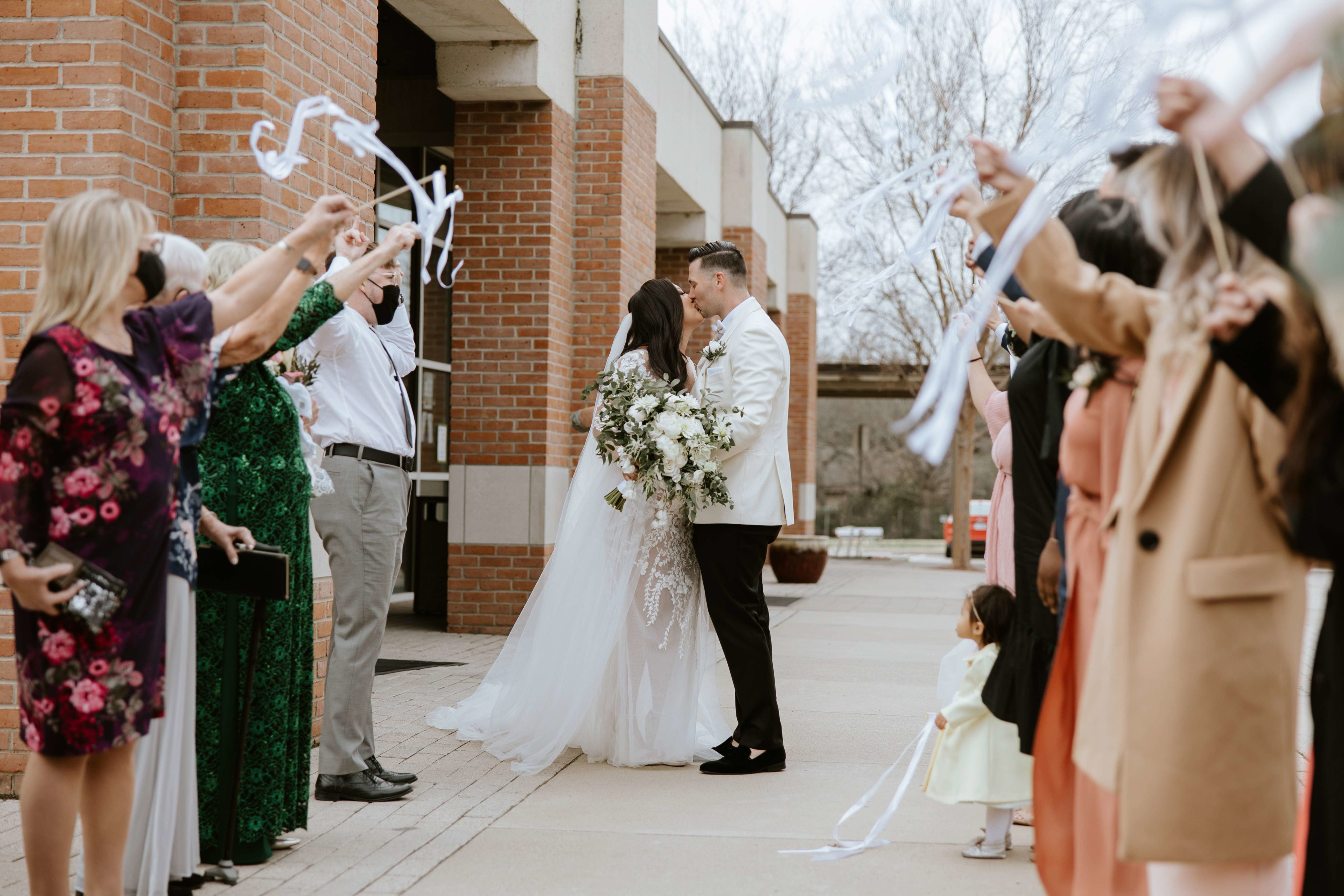 Bride and groom leaving church and kissing