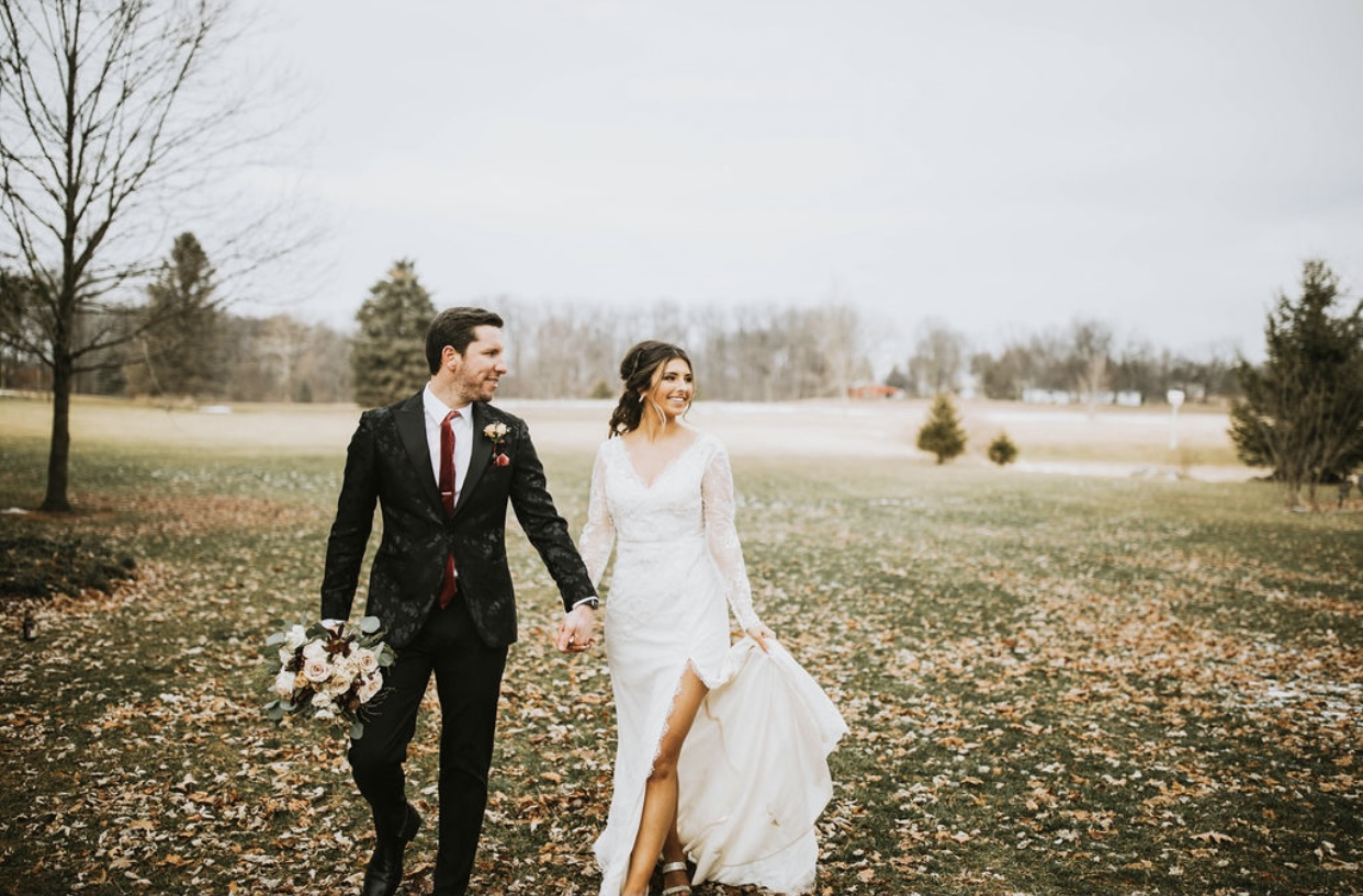 Bride and Groom holding hand in field