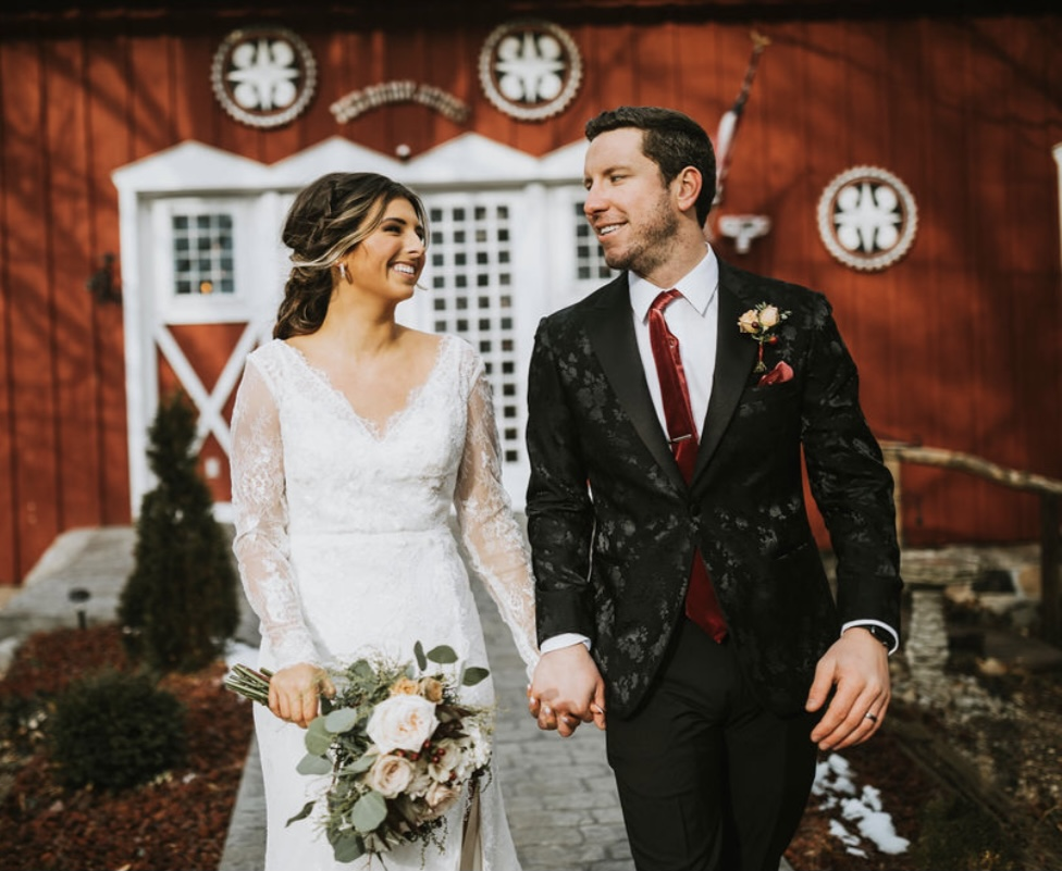 Bride and groom holding hands in front of red barn