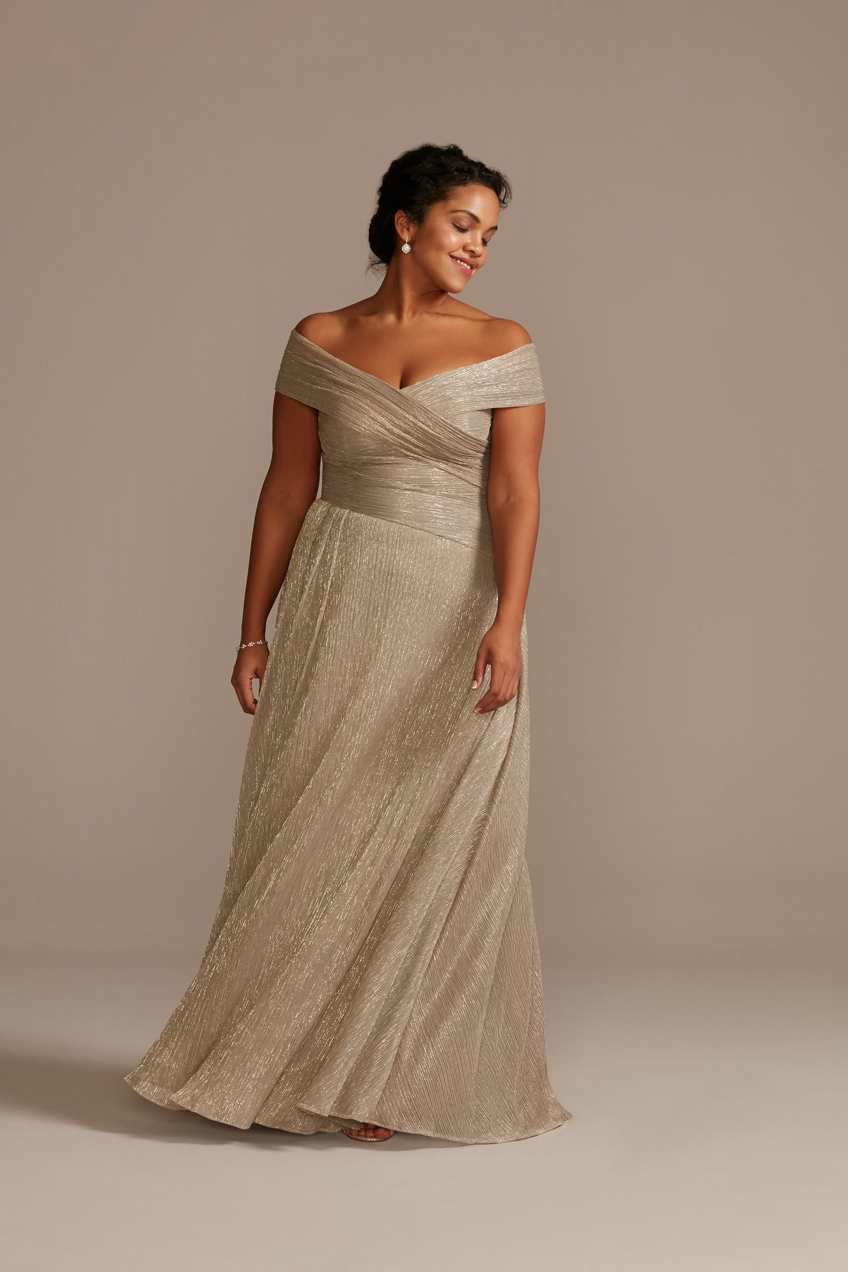 model wearing an off the shoulder, gold metallic a-line mother of the bride dress
