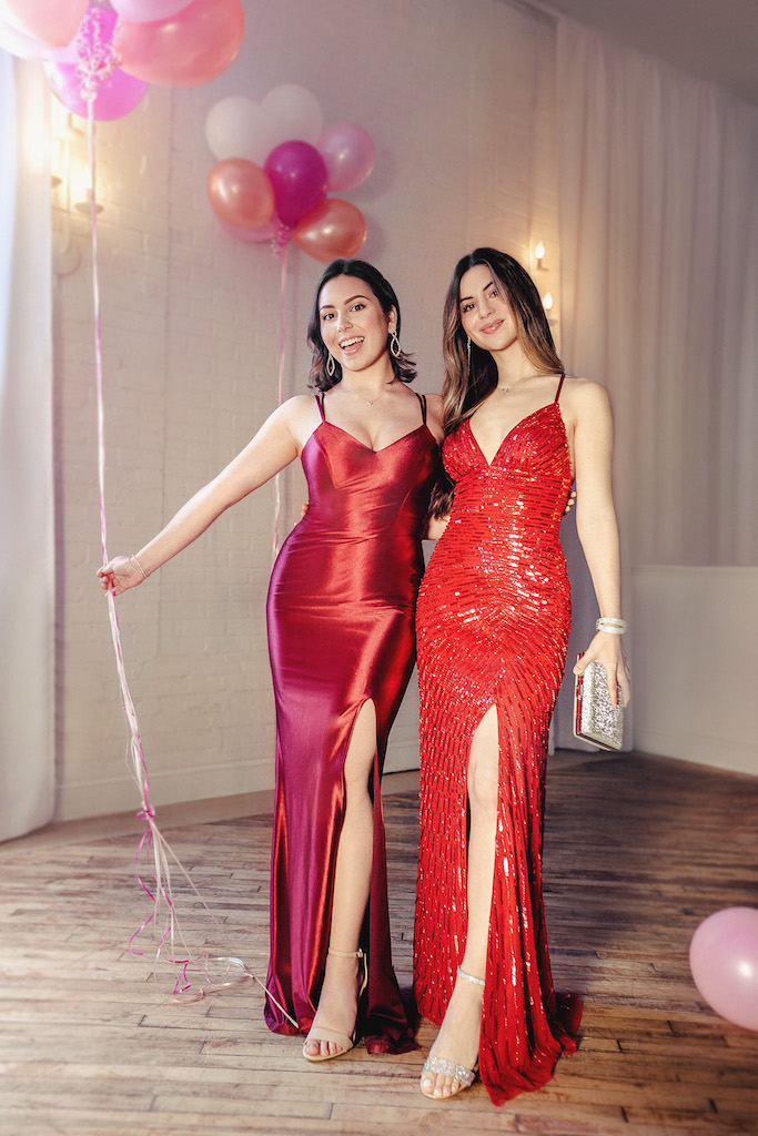 two girls wearing red prom dresses