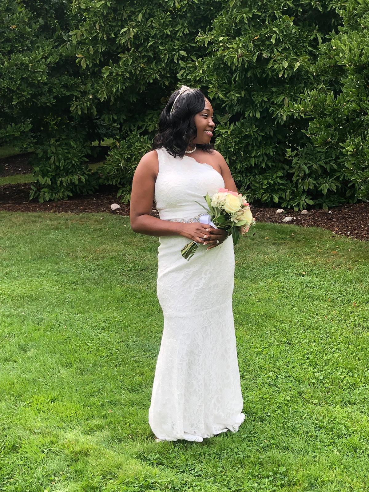 bride wearing a one shoulder sheath wedding dresses in backyard