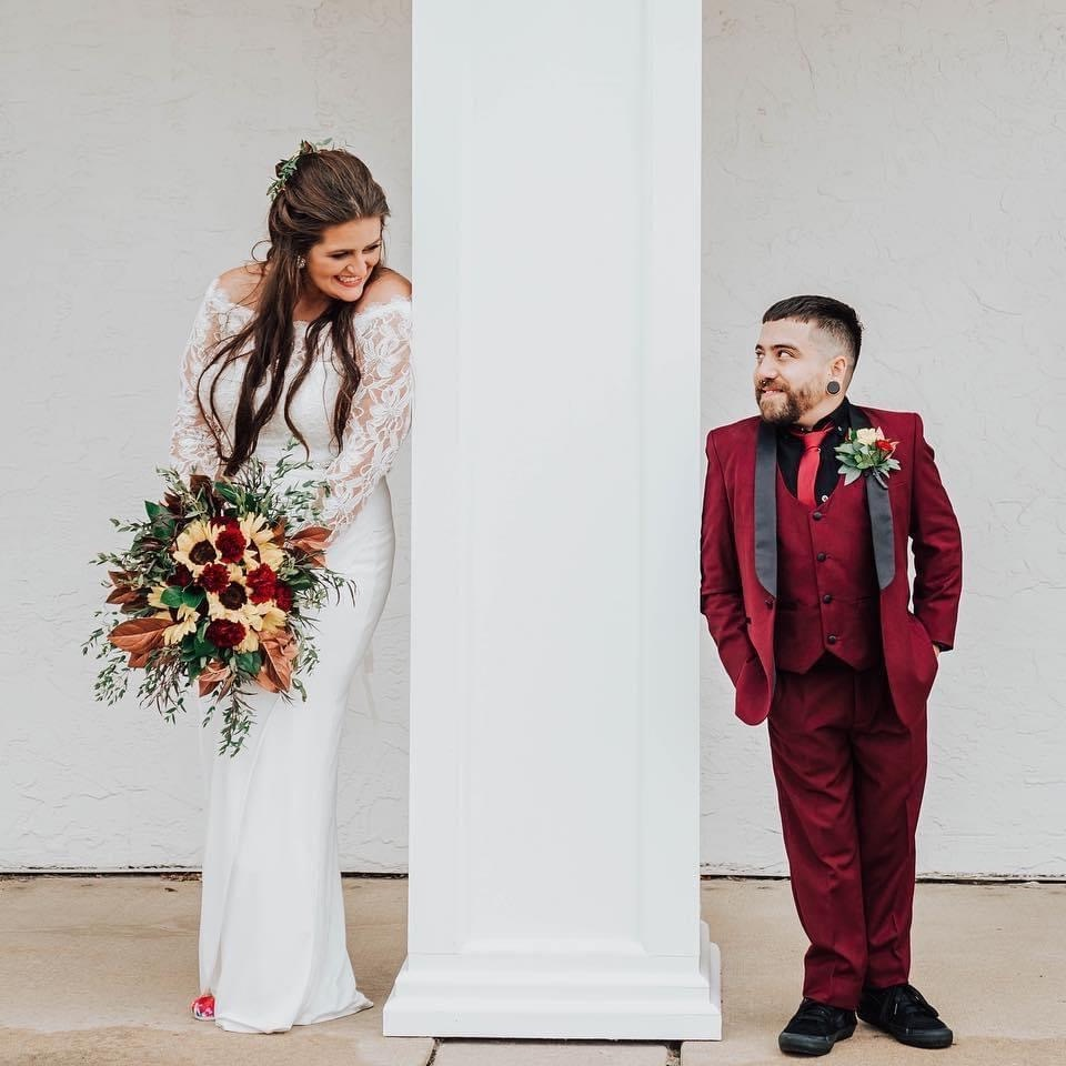 Bride and groom looking at each other on opposite sides of a pillar