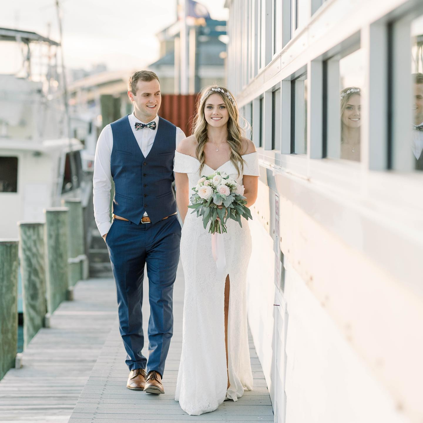 bride and groom walking hand and hand on a dock
