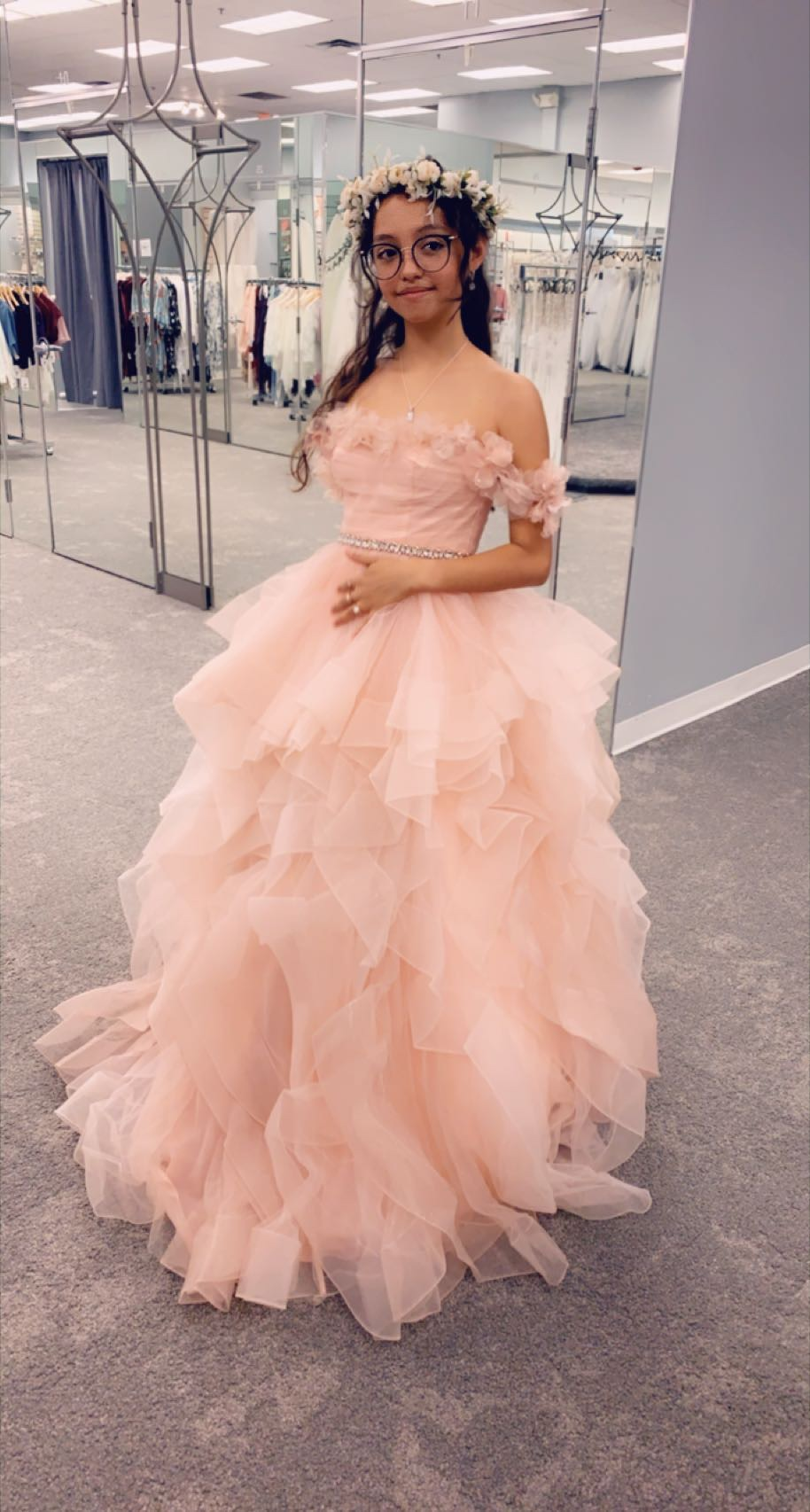 Teenage girl trying on a pink quinceañera dress and flower crown