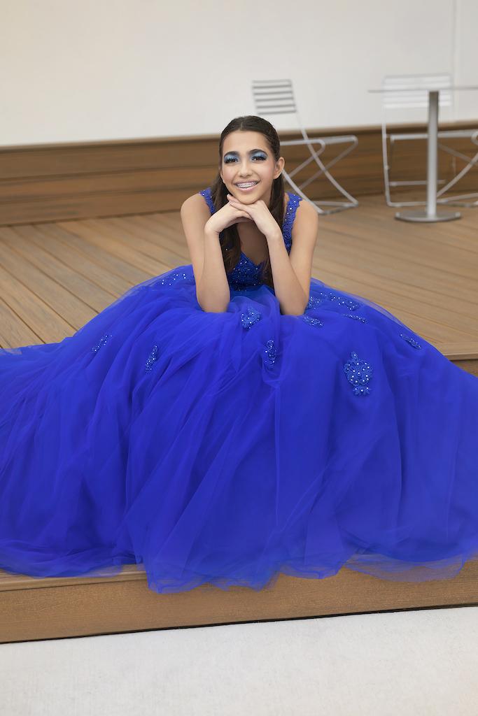 Teenage girl sitting in cobalt blue quinceañera dress