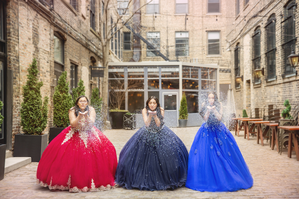 Three teenage girls wearing red, navy, and colbalt quinceañera dresses