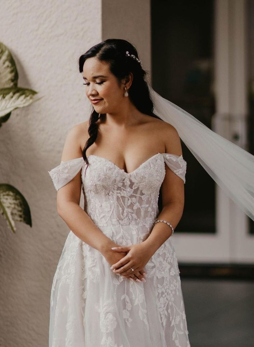 Girl in an off the shoulder wedding dress style.