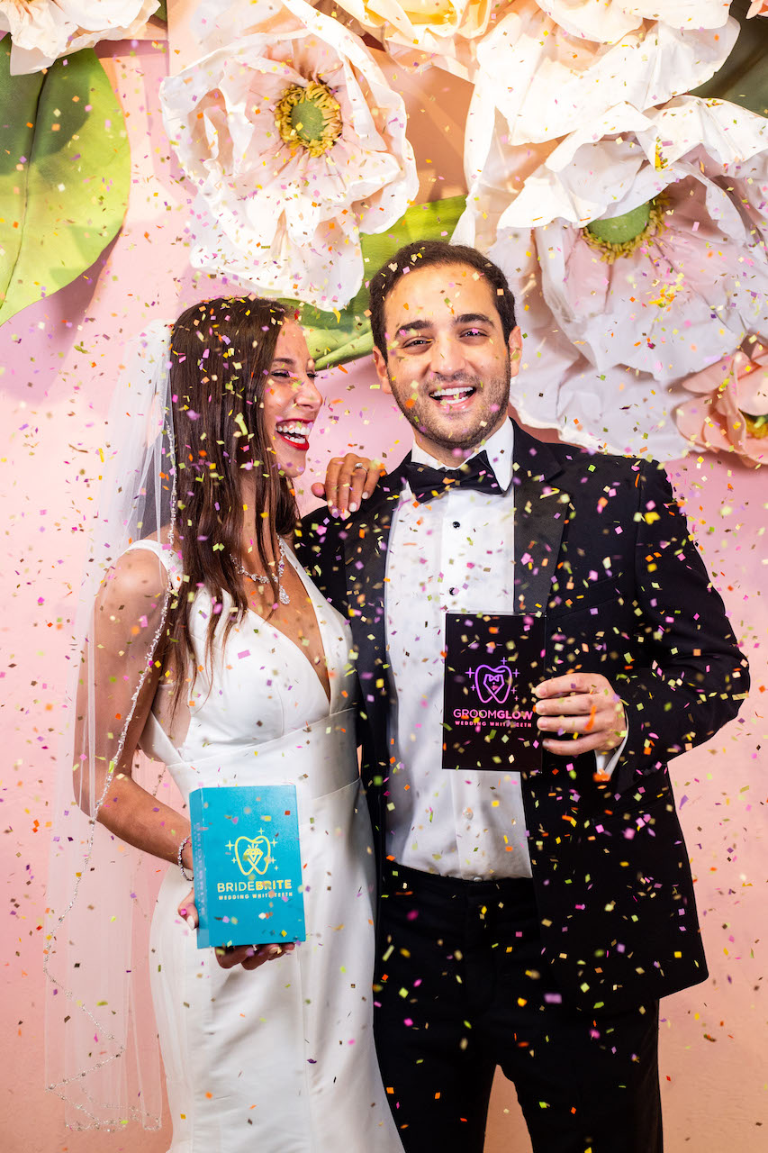 bride and groom holding teeth whitening kits