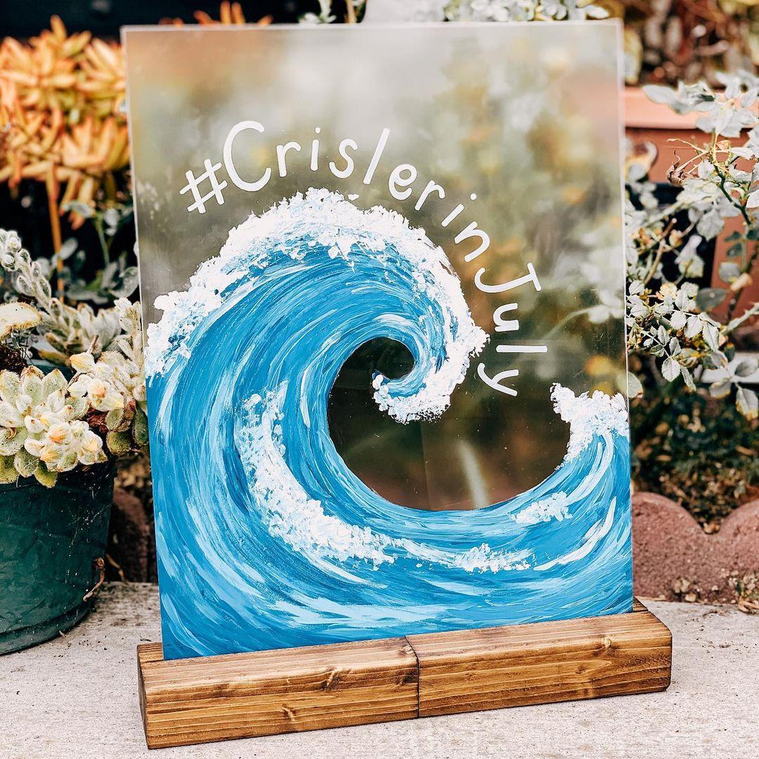 "wedding hashtag idea with blue wave that reads ""#CrislerInJuly"""