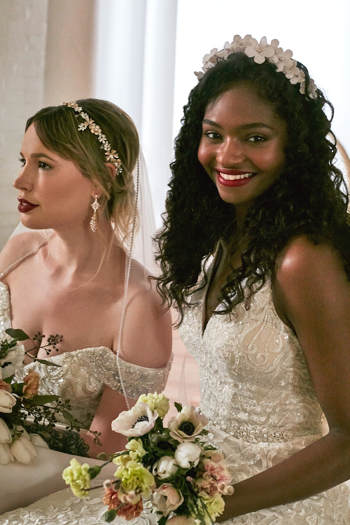 two brides in wedding dresses with pearl and floral accessories