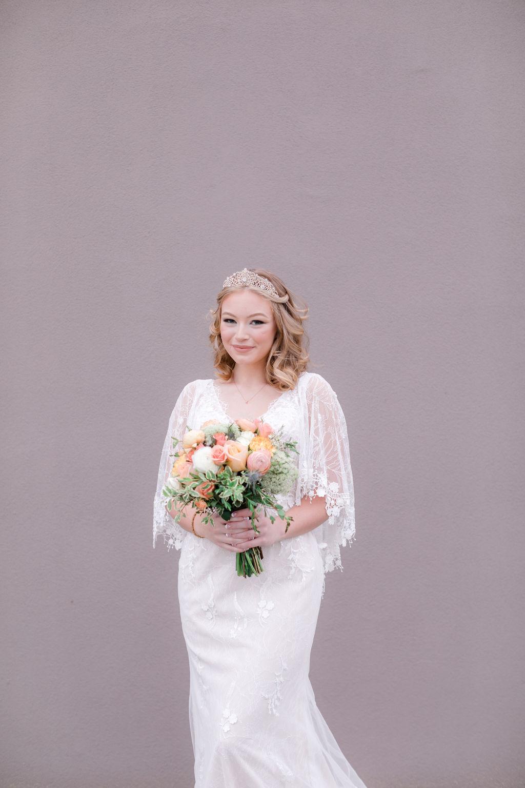 bride wearing boho wedding dress holding pastel colored bouquet
