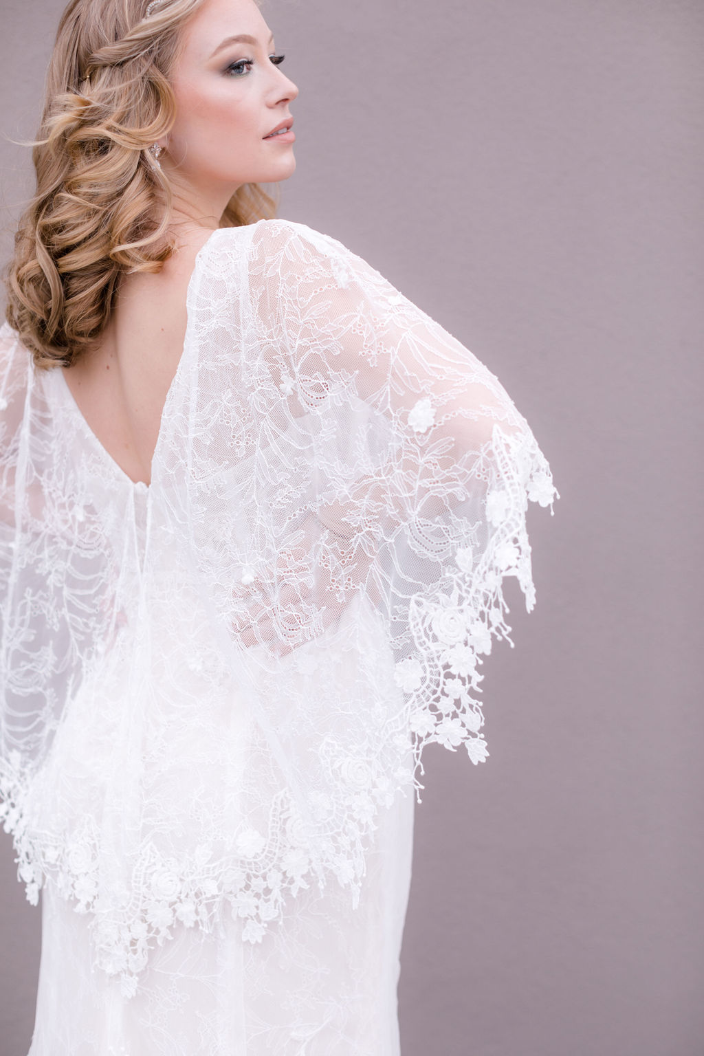 detail hot of bride's wedding dress with lace capelet