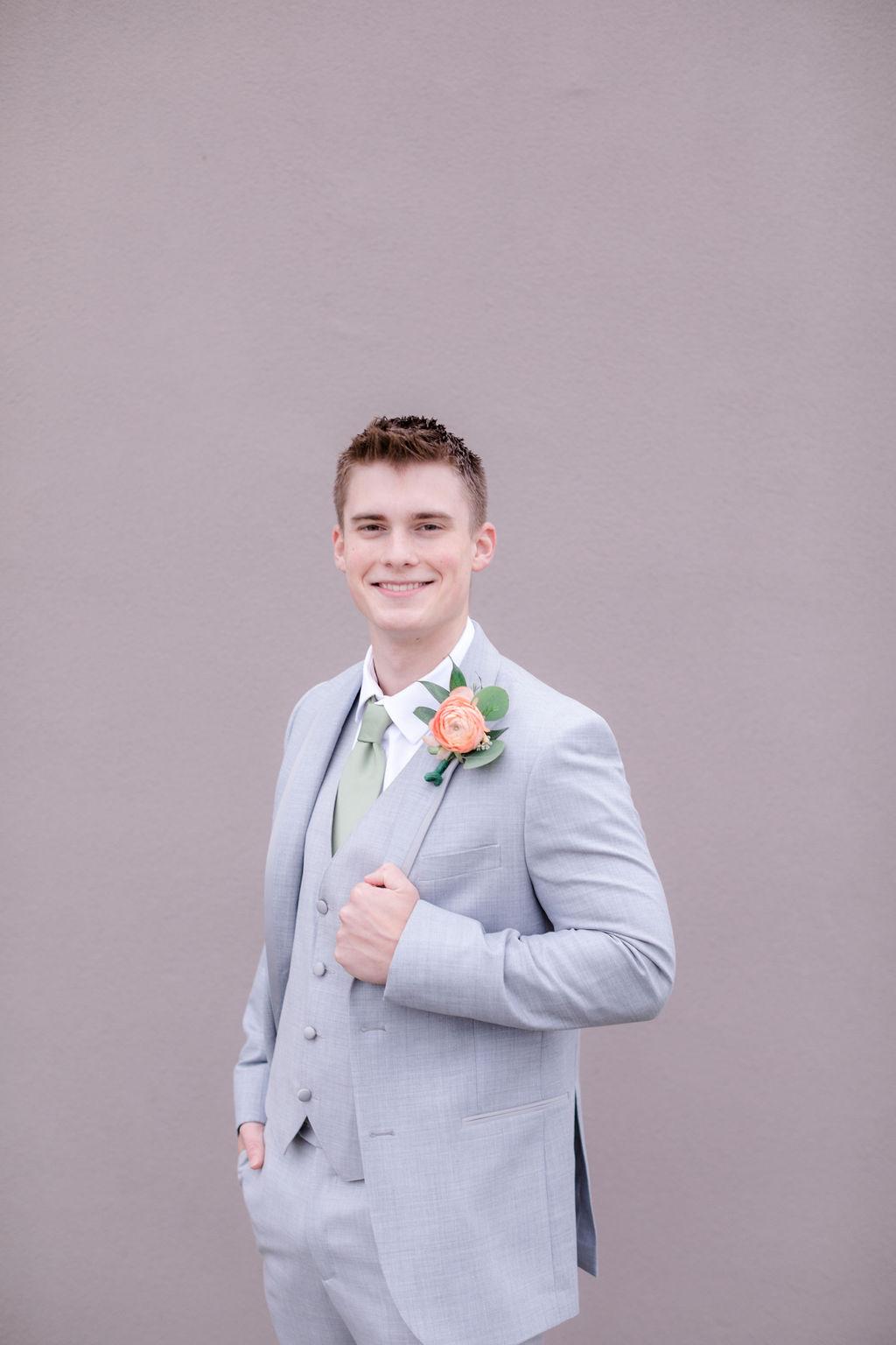 groom wearing gray suit with pastel boutineer