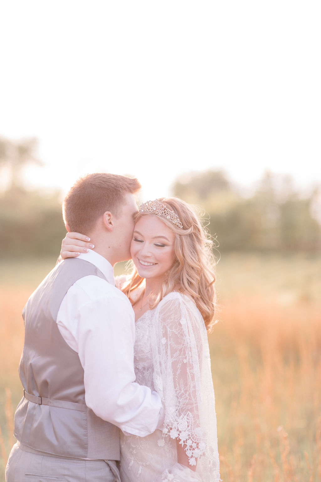 bride and groom embracing at golden hour