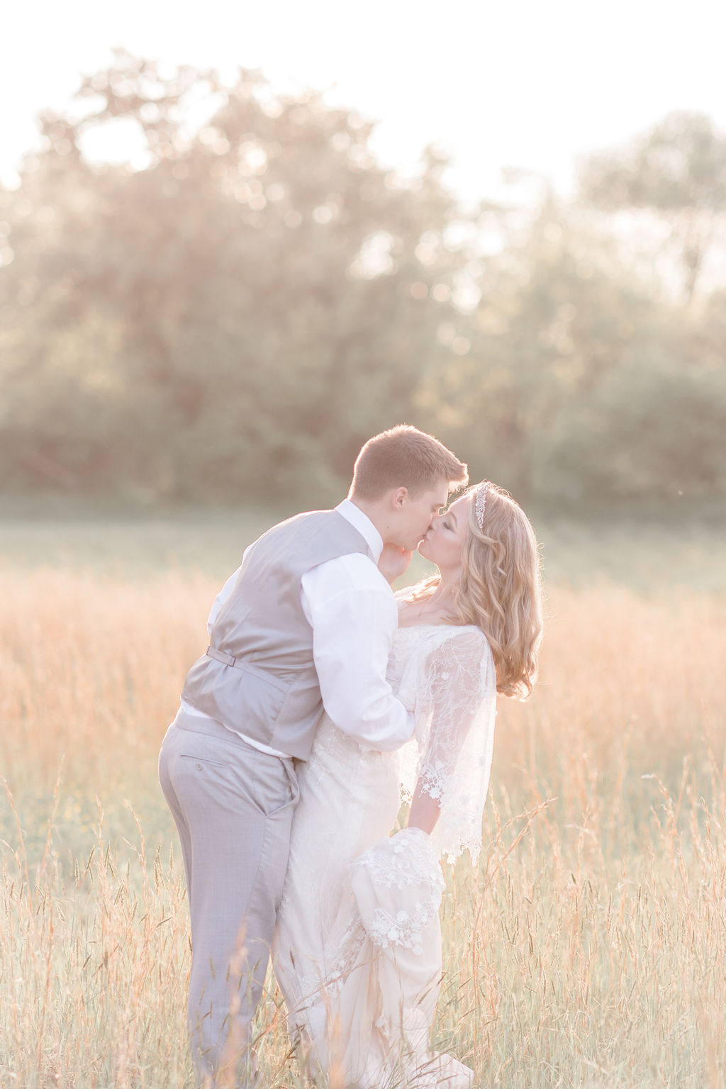 bride and groom kissing at golden hour at dreamy springtime wedding