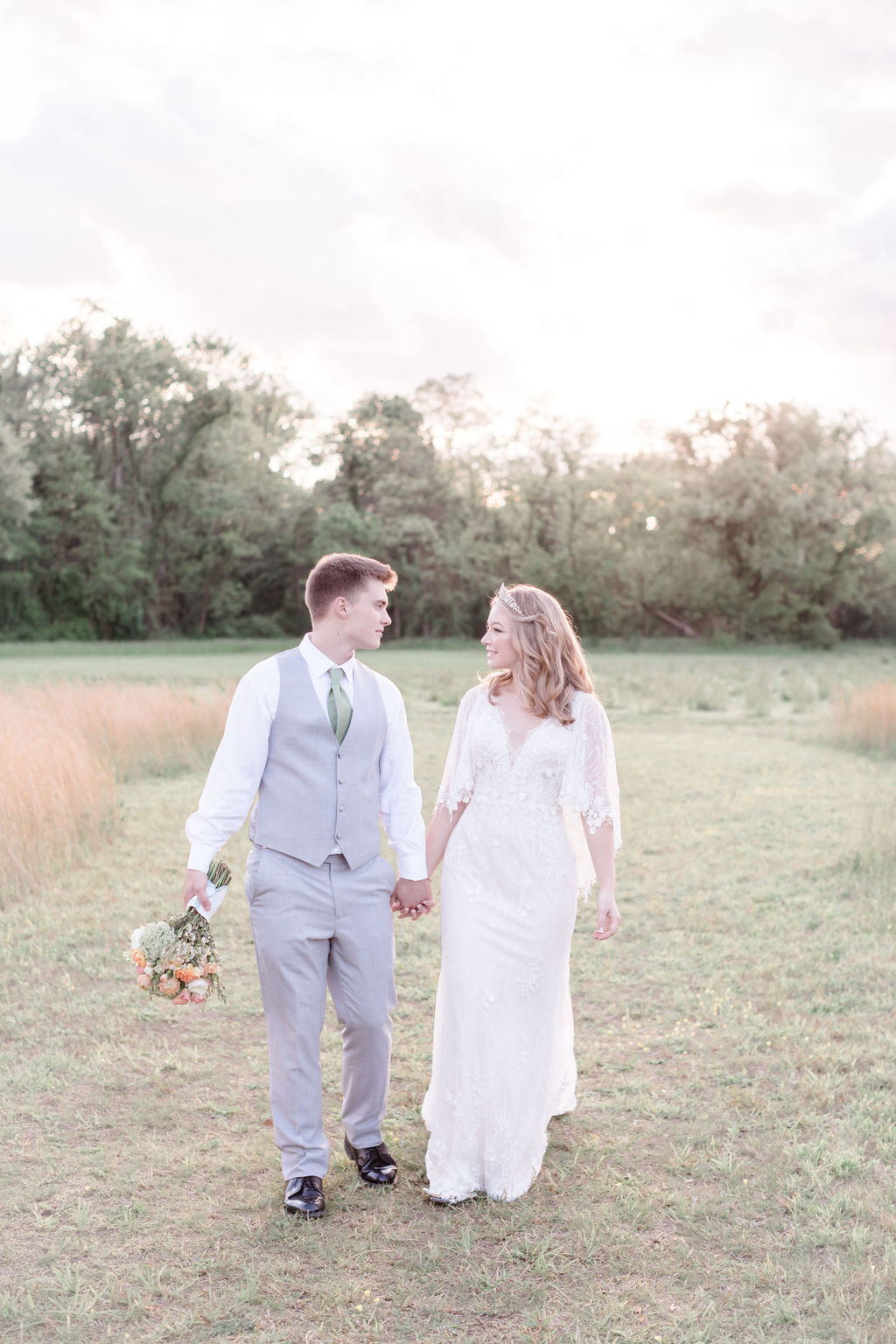 bride and groom looking at each other walking hand in hand in a field at dreamy springtime wedding