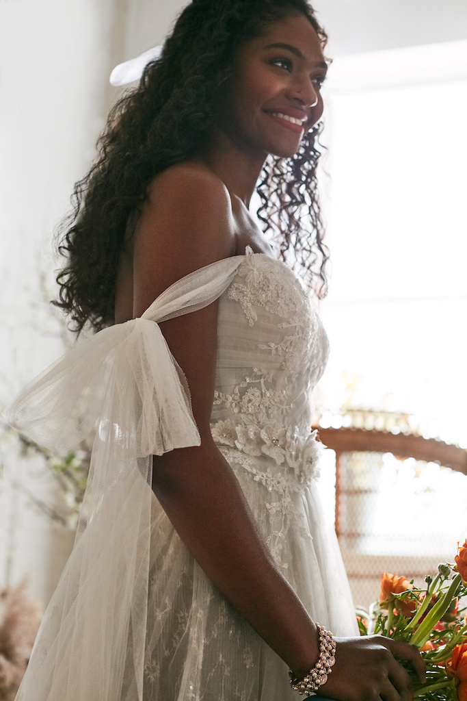 bride wearing tulle wedding dress embellished with beads, sequins, and crystals
