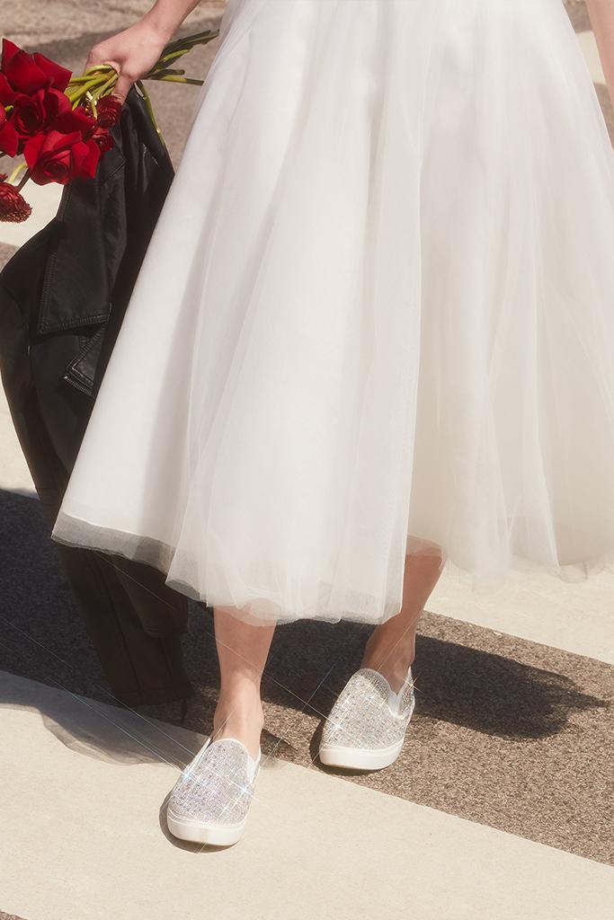 bride walking down city street in crystal slip on sneakers