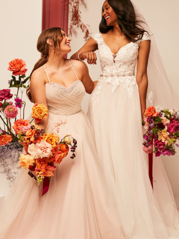 wo brides smiling and laughing at each other in 2021 fall wedding dresses