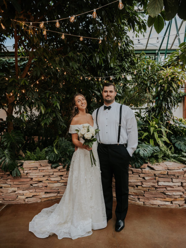 bride and groom standing together at simple and elegant greenhouse wedding