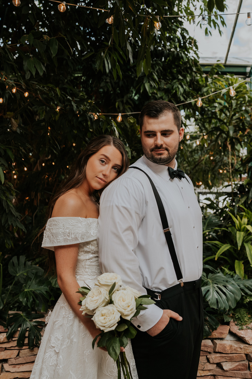bride and groom posing together at simple and elegant greenhouse wedding