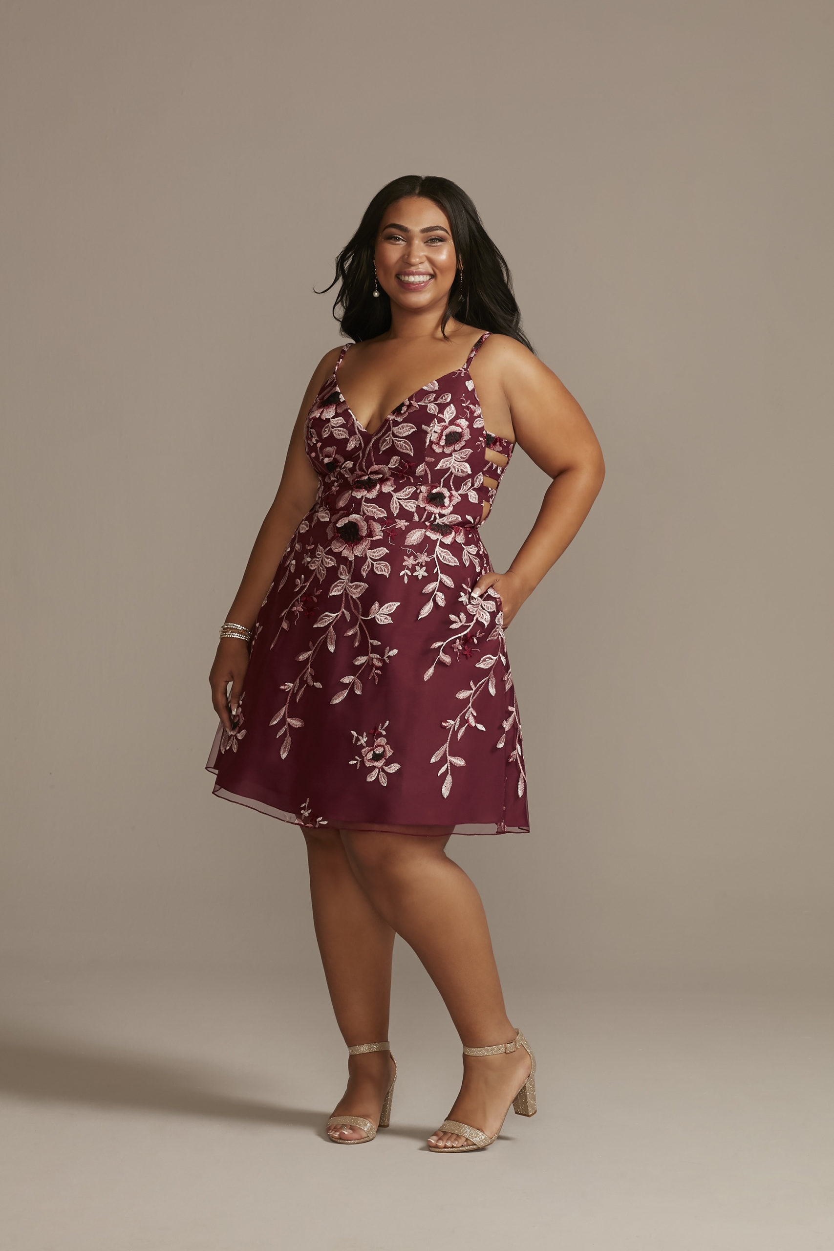 teen wearing floral maroon homecoming dress with side cutouts as homecoming dress idea