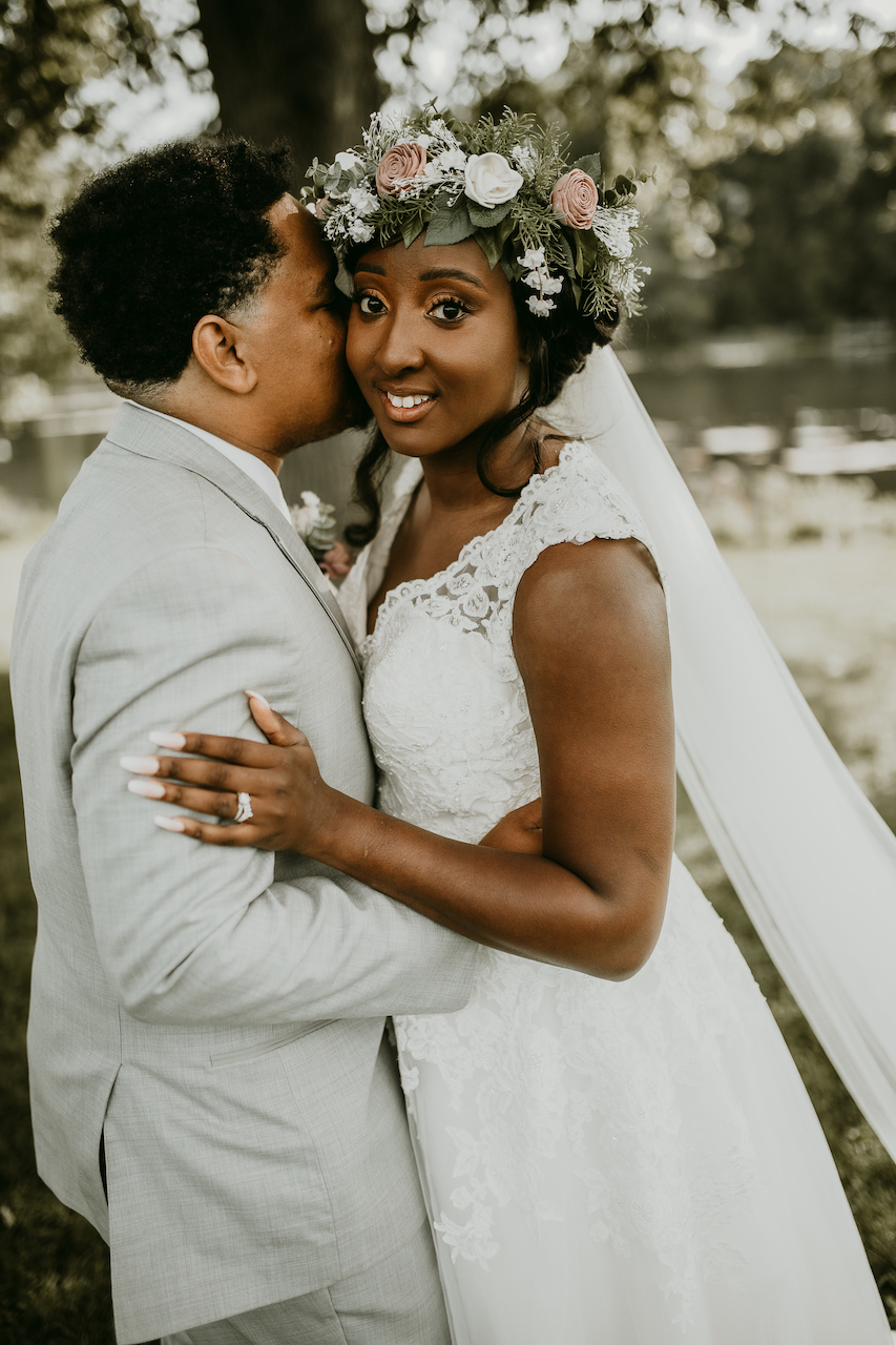 bride and groom embracing at rustic outdoor wedding