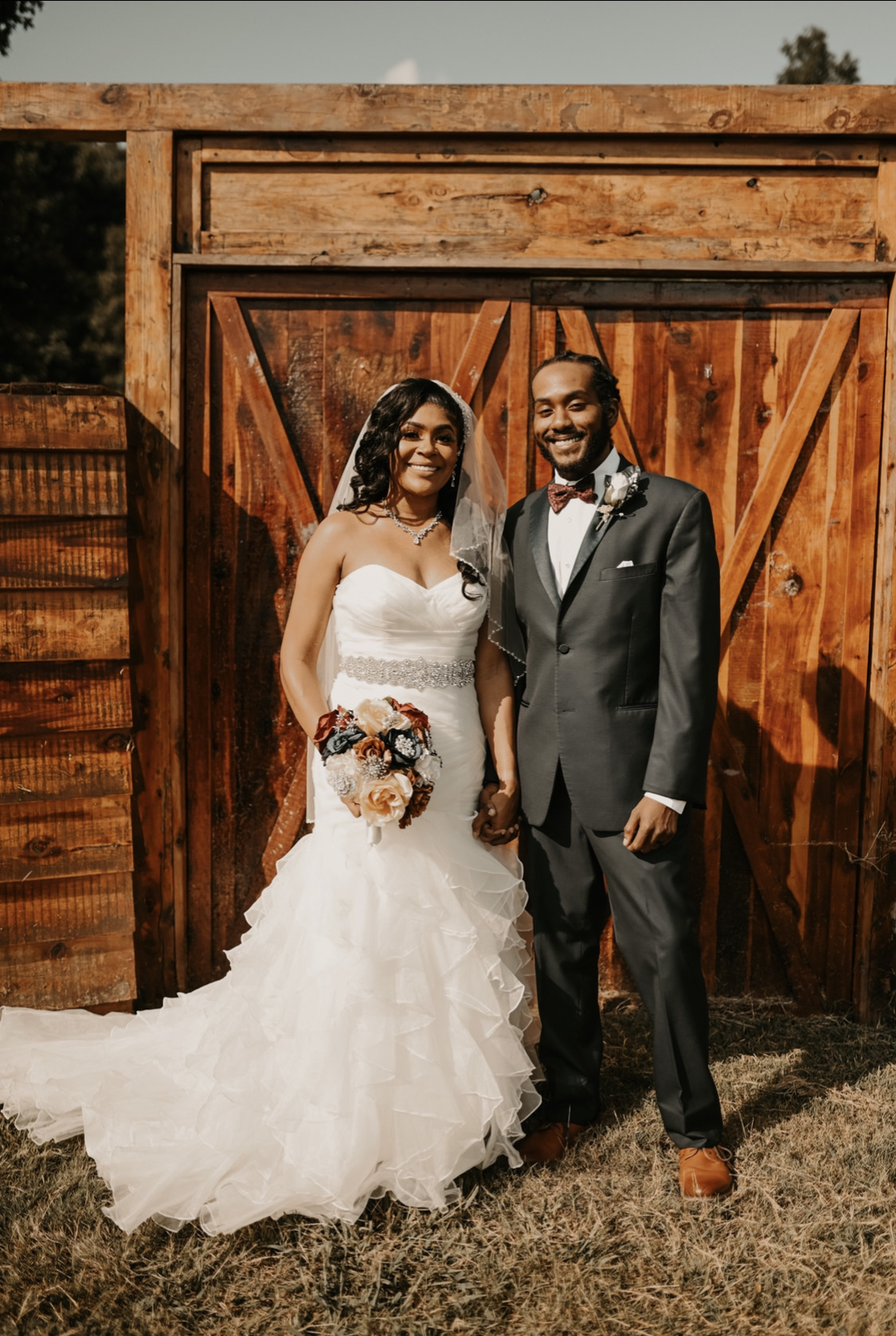 bride and groom in front of barn door at their simple and elegant fall wedding