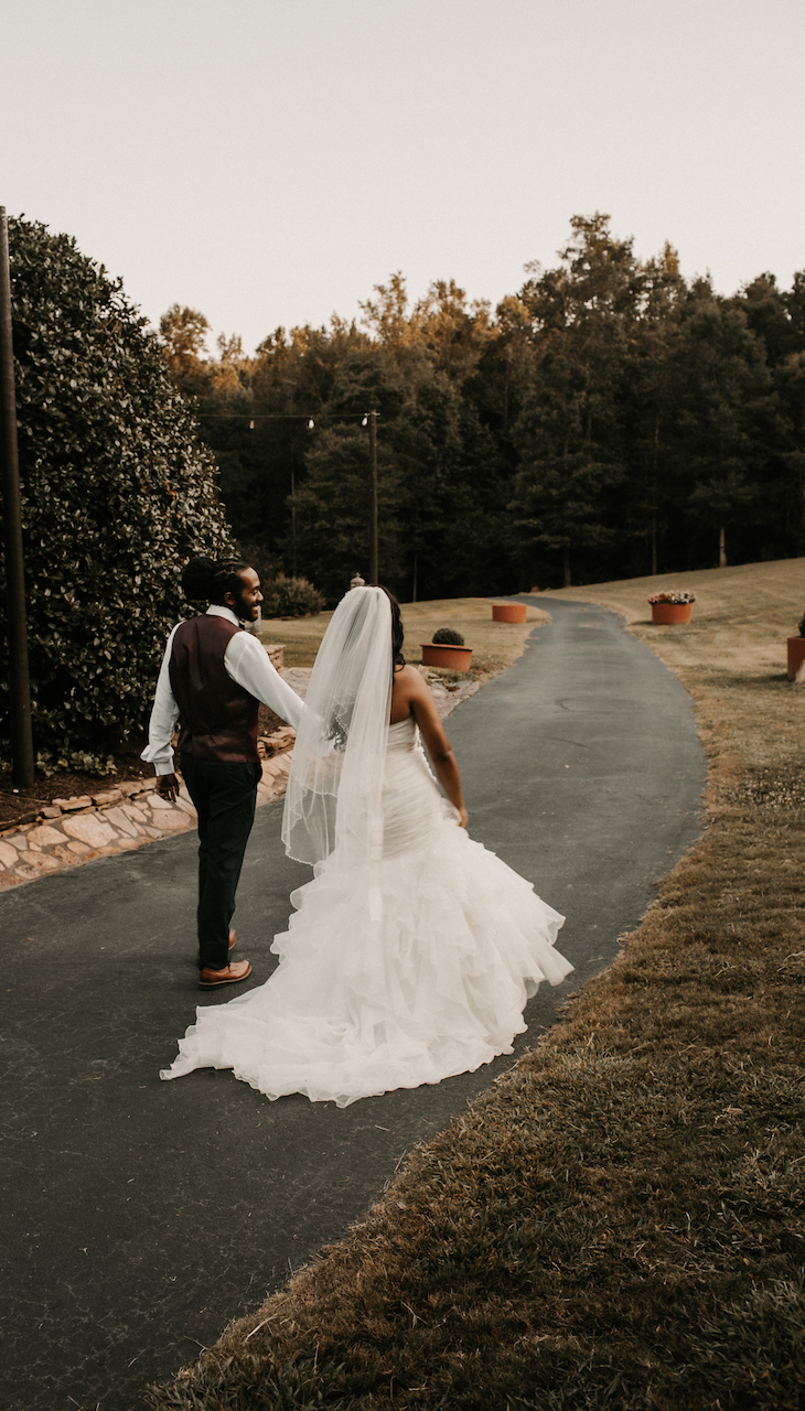 bride and groom walking hand in hand at their simple and elegant fall wedding