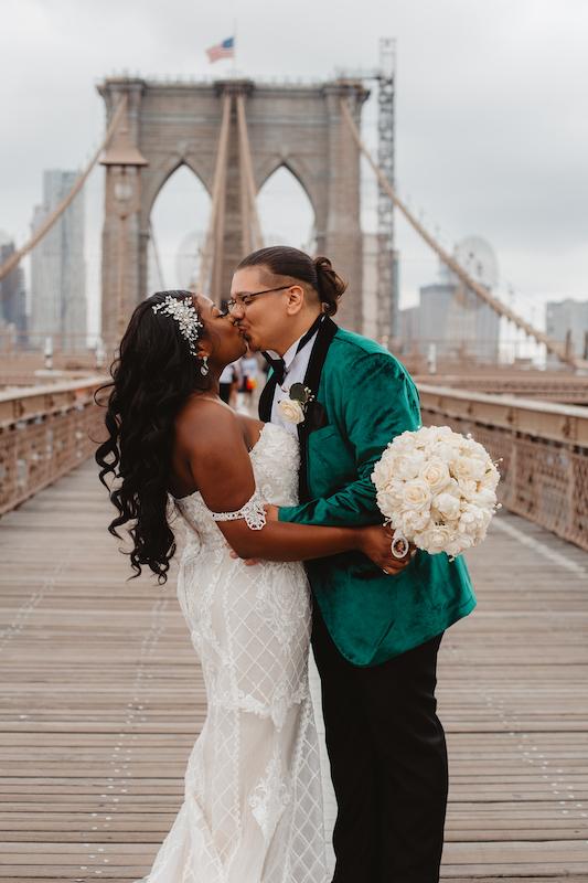 bride and groom kissing on bridge